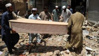 Local residents carry the coffin of a blast victim at the site of a bomb explosion in the main bazaar of Landi Kotal