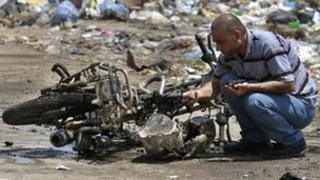 A Palestinian inspects the debris of a destroyed motorcycle after an Israeli air strike in Beit Hanoun, northern Gaza Strip (18 June 2012)