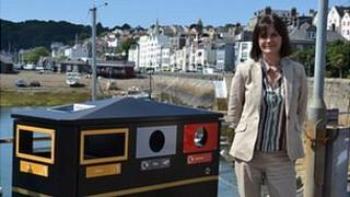 Guernsey States recycling officer Tina Norman-Ross next to a recycling bin in St Peter Port