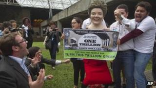 "Environmental activists, one portraying Brazilian President Dilma Rousseff holding a banner symbolizing ""dirty money"" made from fossil fuel subsidies"
