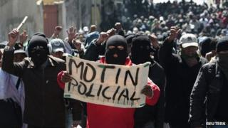 """Police officers hold up a sign saying """"police mutiny"""" at a demonstration in la Paz on 24 June 2012"""