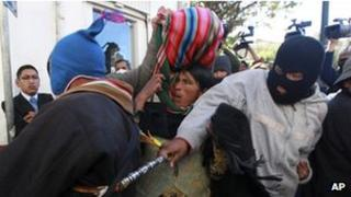 A masked protestor hits an Aymara man trying to enter the plaza in front of the presidential palace