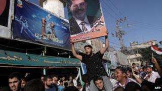 Palestinians celebrate in Rafah town, in the southern Gaza Strip, the victory of the Muslim Brotherhood's presidential candidate Mohamed Morsi (portrait) in Egyptian elections on 24 June 2012