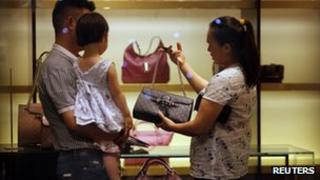 A woman shops for handbags at a Gucci luxury boutique at the IFC Mall in Shanghai June 4, 2012