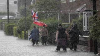 People wade through flood water
