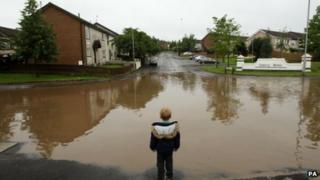 Boy looks at flooded junction