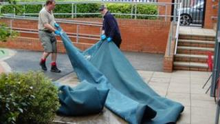 Staff clear up damaged carpets