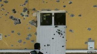 Resident looks at the bullet-riddled town hall in of San Cristobal de las Barrancas