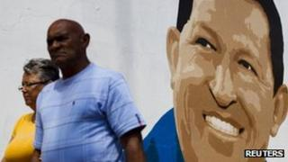 People pass a mural of incumbent Venezuelan President Hugo Chavez in Caracas, 29 June