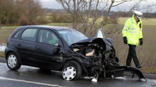 Policeman walks past crashed car by side of the road