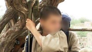 A young boy with a gun standing with Islamist militants in Mali
