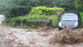 Flood water running down a road in Hebden Bridge