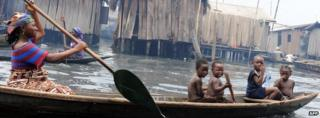Children sit in a canoe with their mother as she navigates through waterways in the Makoko slum in Lagos, Nigeria, on 29 September 2011