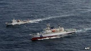 A Chinese patrol boat (L) cruising near a Japan Coast Guard (R) vessel in disputed waters around the East China Sea, 11 July 2012 (Japan Coast Guard handout photo)