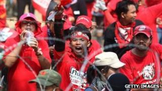 Red Shirt supporters of former PM Thaksin Shinawatra chant slogans at a television satellite centre on April 09, 2010 in Bangkok,Thailand.