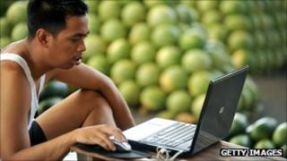water melon vendor checks his laptop