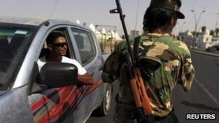 A member of security forces mans a checkpoint in Tripoli, 6 July 2012