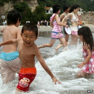 Children playing in waves