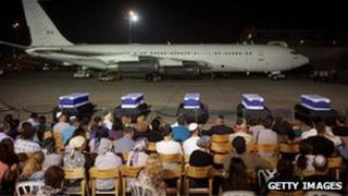 Five coffins draped in Israeli flags set out on the tarmac for a special service with family members