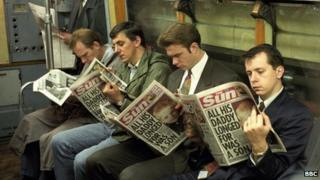 Commuters reading The Sun newspaper
