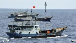 In this photo released by China's Xinhua, Chinese fishing vessels sail past a beacon of Zhubi Reef of the Spratly islands in South China Sea on 18 July, 2012