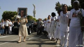 """Members of the """"Ladies in White"""" opposition group march beside the funeral procession of Oswaldo Paya on 24 July 2012"""