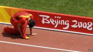Liu Xiang clutching his ankle during the warm up prior to the first round of the men's 110m hurdles at the Bird's Nest during the 2008 Beijing Olympic Games, 18 Aug 2008