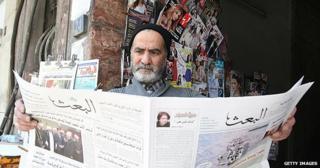 Man reading Al-Baath newspaper