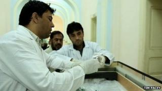 Chief curator Fahim Rahimi and staff open the crates containing the recovered artefacts
