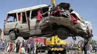 Bus wreckage being lifted by a crane