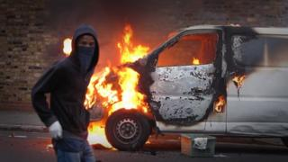 A hooded youth walks past a burning van in Hackney on 8 August 8, 2011