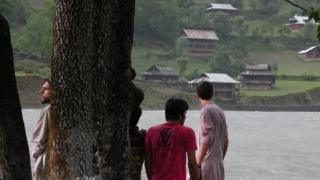 Keran villagers look over the Neelum river at houses on the Indian side