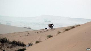 A member of the Egyptian security forces takes position on a sand dune during an operation in the northern Sinai peninsula on August 08, 2012