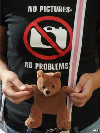 A Belarusian opposition activist holds a teddy bear as she wears a satirical t-shirt near a court in Minsk on 9 August