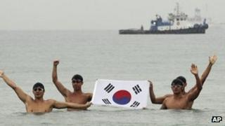 Swimmers holding South Korea's flag in the port city of Uljin