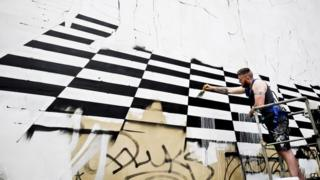 An artist rides on a cherry picker as he begins a huge fencing graffiti mural on a massive wall on Broad Street