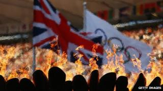 The Olympic Cauldron burns in front of the Union Jack and Olympic flag