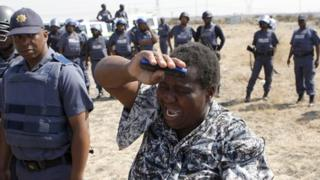 A local women cries as she confronts a police officer during a protest against the killing of miners by South African police