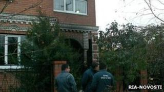 Emergency workers stand outside the house where the murdered occurred (file image from 2010)