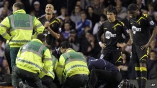 Players around prone footballer