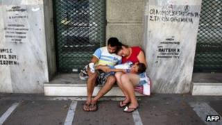 Family begs on the street of the Greek capital Athens on 13 June 2012