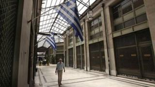 """Arcade of shops with """"for sale"""" signs on their windows in Athens (22 August 20120)"""