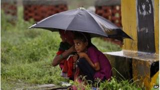 Women protect themselves with an umbrella from monsoon showers at Bharatpur in Rajasthan state, India