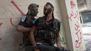 Free Syrian Army fighters take cover as they exchange fire with regime forces in the Salaheddin neighbourhood of Syria's northern city of Aleppo on Wednesday