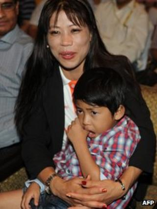 Indian boxer MC Mary Kom with one of her twin boys in her lap