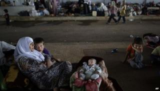 A Syrian family who fled their home take refuge at the Bab Al-Salameh border crossing with Turkey near the Syrian town of Azaz, 29 August 2012