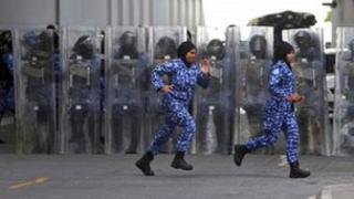 Two women riot police officers run in front of fellow officers standing as a barricade in Male, Maldives, 29 August 2012.
