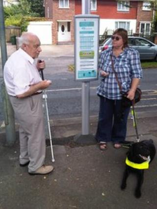 Two people using a talking bus stop