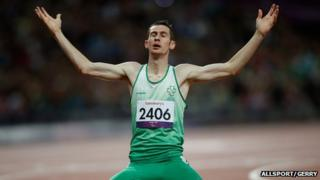Michael McKillop kneels on the track after winning gold