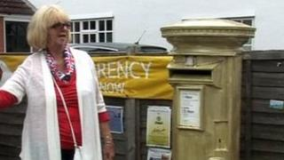 A member of the public with the gold postbox
